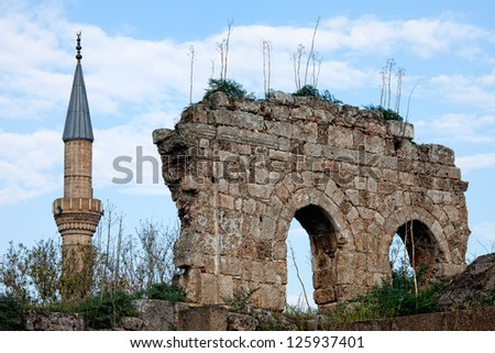 View of minaret of Tekeli Mehmet Pasa Mosque next to ruins in Antalya Turkey - stock photo