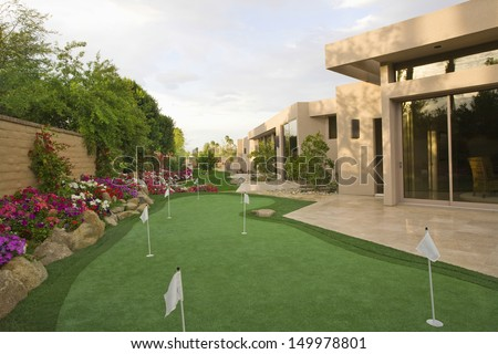 View of mini golf course in garden by luxury house - stock photo