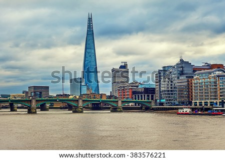 View of modern buildings along Thames river and Shard on background under cloudy sky in London, UK.