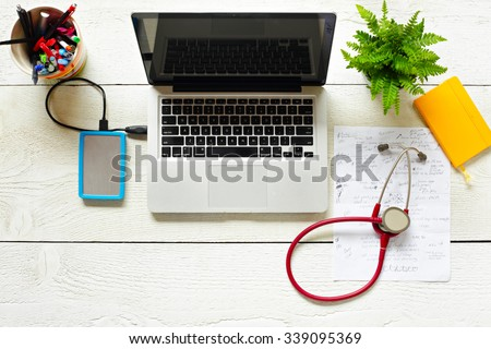 View of modern doctor's desk from above including real doctor's notes - stock photo