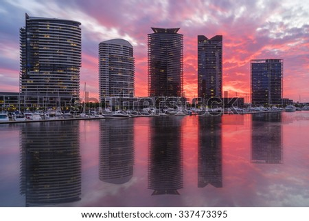 View of modern luxurious apartments and marina in Docklands, Melbourne with reflection during sunset.  - stock photo