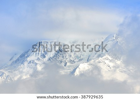 view of Mont Blanc through the clouds in winter - stock photo