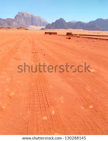 View of motor car tracks on the red sand against the background of distant blue mountain range in Wadi Rum desert, Jordan - stock photo