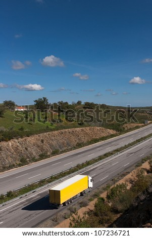 view of motorway with yellow truck - stock photo