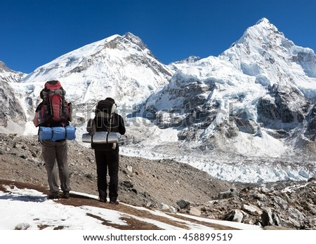view of Mount Everest, Lhotse and Nuptse from Pumo Ri base camp with two tourists on the way to base camp, Sagarmatha national park, Khumbu valley - Nepal