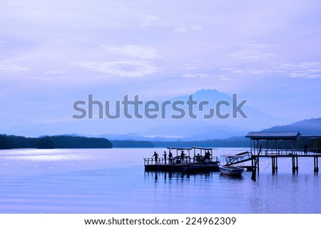 View of Mount Kinabalu in the far horizon seen from the Jetty Mengkabong, Sabah Borneo, Malaysia. After sunrise. - stock photo