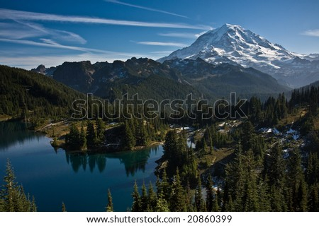View of Mount Rainier on a clear blue day with a still mountain lake in the foreground and a dusting of snow in the lower hills - stock photo