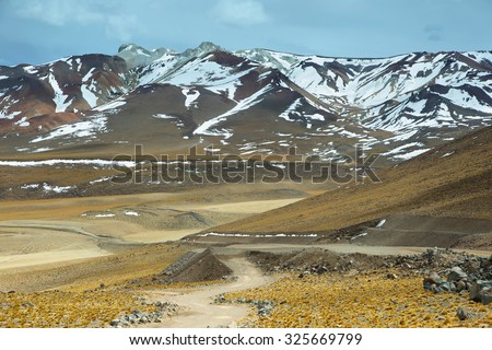 View of mountains and dirt road in Sico Pass, Chile - stock photo