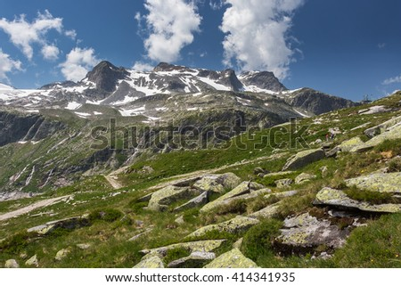 View of mountains in summer. Snow-capped mountains in Austrian Alps. Sky with clouds. Hill overgrown with grass in foreground. People walking along hiking trail - stock photo