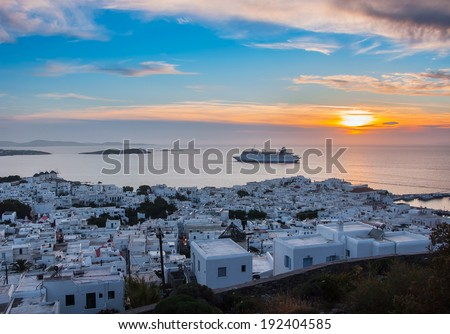view of Mykonos, windmill and old port with cruise ship at sunset - stock photo