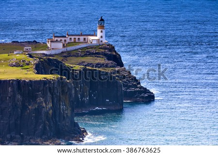 View of Neist Point lighthouse and rocky ocean coastline on the Isle of Skye, Scotland - stock photo