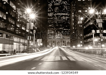 View of New York city at night with car's lights streaks passing by in a vintage-like shot with the Grand Central Terminal in the background. - stock photo