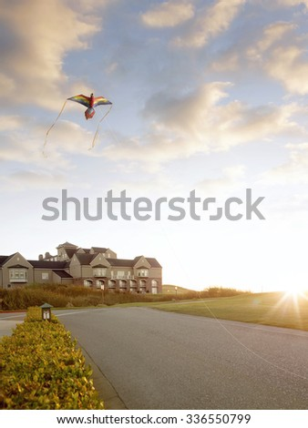 view of nice countryside style house and  paper kite during  summer sunset - stock photo