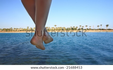 view of nice smooth woman's legs hanging on beach backgound