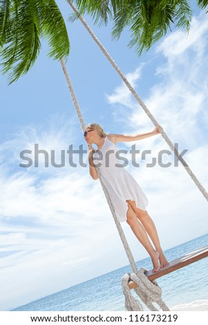 View of nice tropical  beach  with  girl on swing