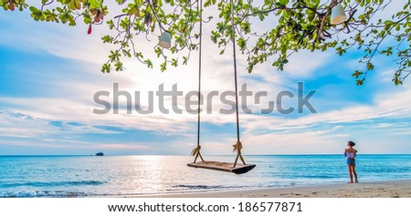 View of nice tropical beach with young beautiful girl on swing  - stock photo