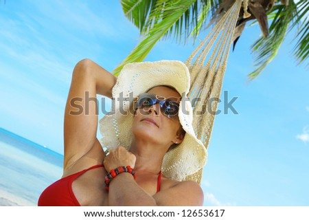 view of nice woman lounging in hammock in tropical environment