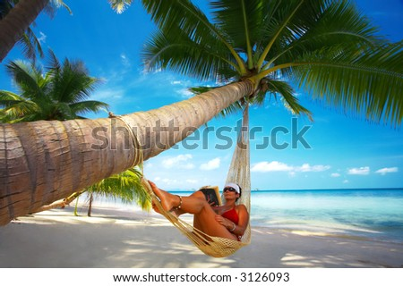 view of nice woman reading a book in hammock in tropical environment - stock photo