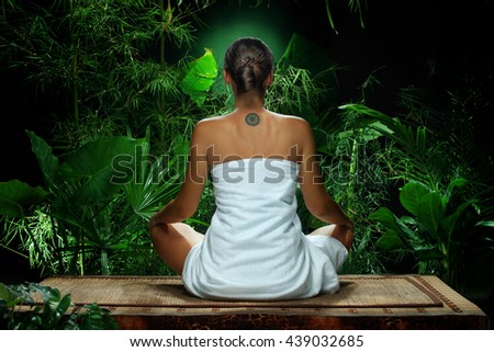 View of nice young woman meditating in spa environment - stock photo