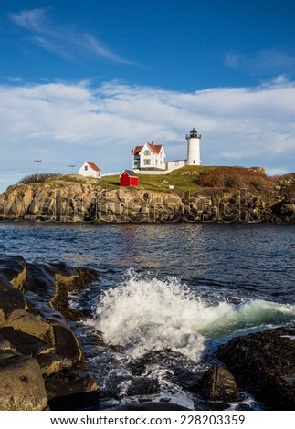 View of Nubble lighthouse in Maine in New England USA showing rocky coastline against blue sky shot vertically with surf splashing against coastline in foreground. - stock photo