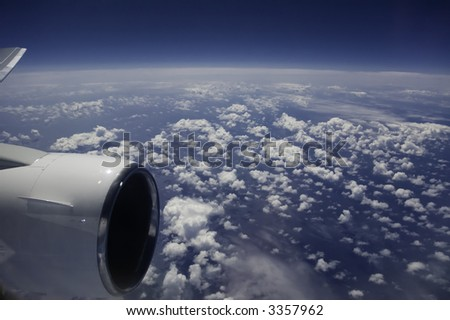 view of ocean and clouds from jet airplane window - stock photo