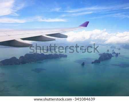 View of ocean and islands from airplane window - stock photo