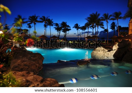 View of ocean from luxury hotel at night, Kaanapali, Maui, Hawaii with palm trees. - stock photo