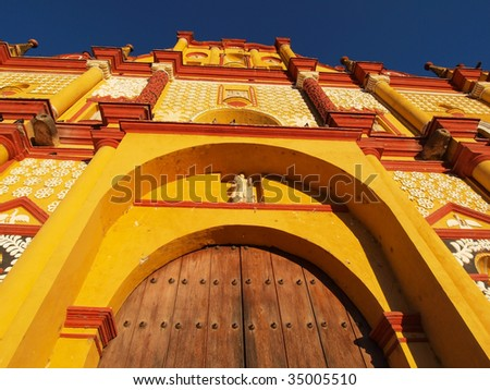 View of old, brightly painted colonial church in town center of San Cristobal de las Casas, Chiapas, Mexico. - stock photo