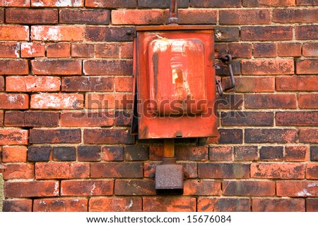 view of old metal alarm box on brick wall