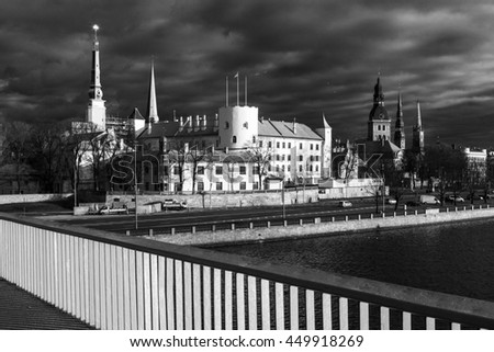 View of old Riga castle with Daugava river in foreground on cloudy evening before sunset. Black and white photograph.