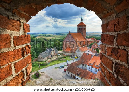 View of old town and church through the castle tower window, Reszel, Warmia, Poland - stock photo