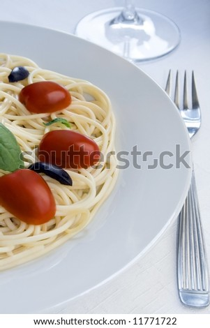 View of one half of a spaghetti dish with cherry tomatoes, black olives and basil. - stock photo