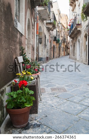 View of one typical street in Ortigia, the old part of Syracuse, and some ornamental flowered vases - stock photo