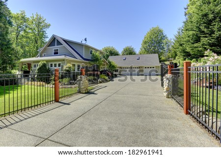 View of open entrance iron gates and driveway. - stock photo