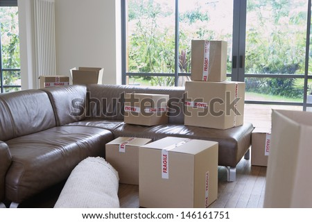 View of packed cardboard boxes in living room of a new home - stock photo