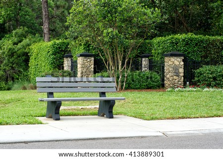 View of park bench / bus stop on road in Naples florida, with sidewalk, vegetation, and stone posts.