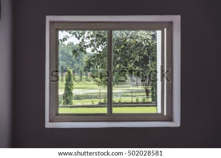 View of park through window from inside of a building.