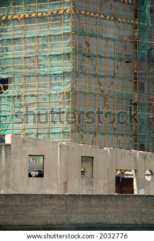 View of partly demolished building with a new development behind being built in Shanghai, China. - stock photo