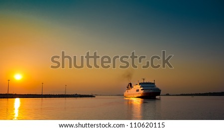 view of passenger ferry boat in open waters in Greece at sunrise. - stock photo