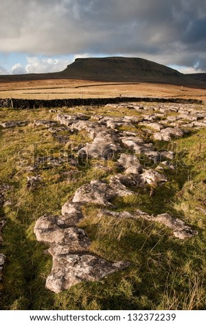 View of Pen-y-Ghent across limestone crags in Yorkshire Dales National Park - stock photo