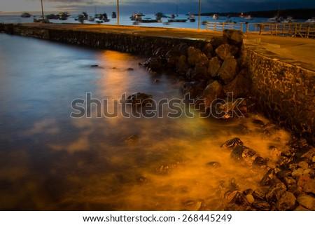 View of pier in San Cristobal island, Galapagos, during sunset, Ecuador - stock photo