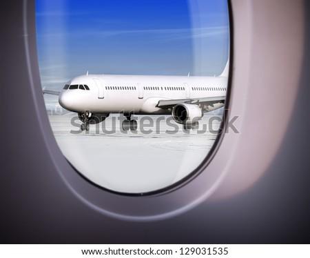 view of plane on runway through window, airport - stock photo