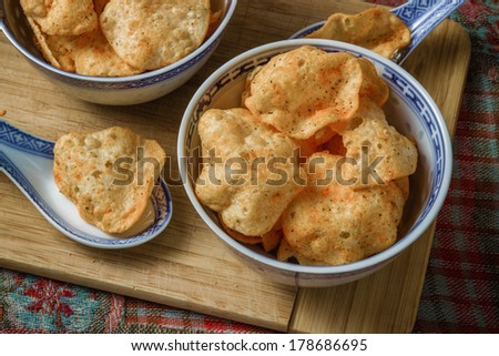 View of potato chips in bowls on a cutting board