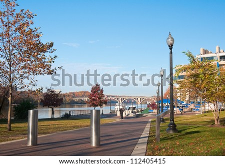 View of Potomac River and Frances Scott Key Bridge from Washington Harbor, Georgetown Waterfront, Washington DC. Early morning light in Fall. - stock photo