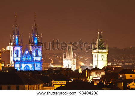 View of prague rooftops with the blue illuminated spires of Tyn church in Old Town Prague, Czech Republich - stock photo