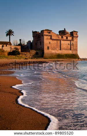 View of Pyrgi castle in Italy with calm sea and foamy waves on brown sand