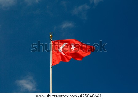 View of red and white Turkish flag with a moon and star on bright blue sky background.