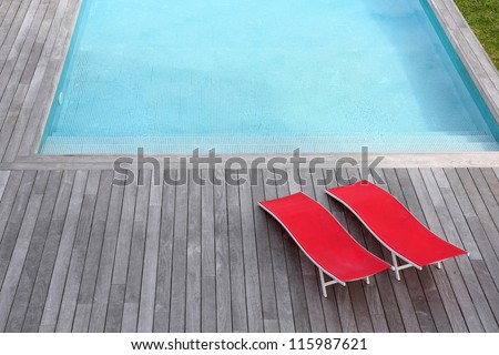 View of red long chairs set by swimming-pool - stock photo