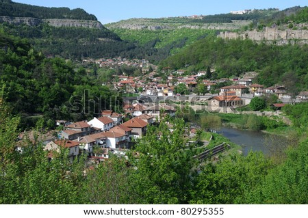 View of residential area of Veliko Tarnovo, wall of Tsarevets fortress and Yantra river - stock photo
