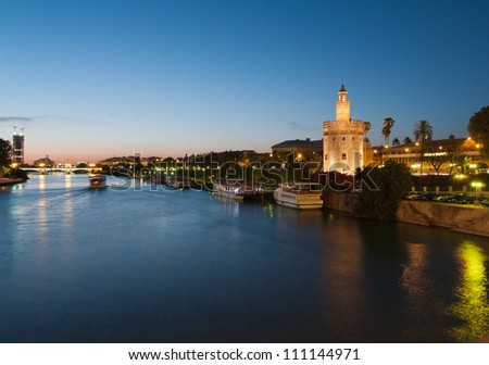 view of river Guadalquivir in Seville, Spain with Golden Tower (Torre del Oro) and Triana bridge at night - stock photo